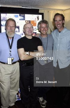 LONDON - JUNE 27: (EMBARGOED FOR PUBLICATION IN UK TABLOID NEWSPAPERS UNTIL 48 HOURS AFTER CREATE DATE AND TIME) (L-R) Genesis manager Tony Smith is presented with an artwork of Genesis posters and album covers backstage as a thank you from band members Phil Collins, Tony Banks and Mike Rutherford, following Collins' concert performance at Wembley, on June 27, 2004 in London. (Photo by Dave Benett/Getty Images))