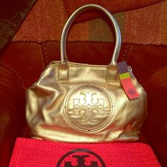 Final Sale Authentic Tory Burch Gold  Stacked logo classic Tory Burch tote. This tote is great in size, never will be full. New with tags and dust bag. Own it, it is gorgeous!!!!No trades No pp Price is firm. Some de coloration on the handles for being inside a dust bag. Tory Burch Bags