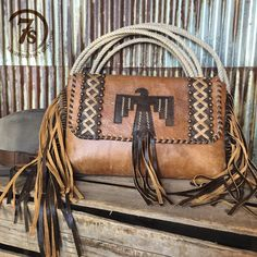 - The epitome of a retro vibe western clutch - Large style for a certain statement maker - Soft rustic saddle tan leather - Bronze leather thunderbird, fringe and whip stitch accents - Champagne leath