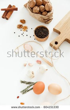 Vegetables, nuts, beans, cinnamon, rosemary, chicken eggs, other food and kitchen appliances lie on a white background. Space for text, daylight, vertical image.
