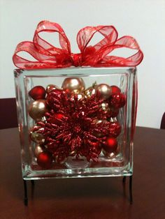 DIY   Snowflake & Ornaments filled Glass Block Table Decoration - Large Glass Block (Hobby Lobby) filled with red/gold ornaments (Dollar Tree). Wrap the block edge with wire-edge ribbon and tie a bow on top (Dollar Tree has 9ft rolls for one dollar). Glue flat snowflake ornament to front of glass block. Insert into to metal stand (Hobby Hobby).  Makes a holiday table decoration for approx. $15.00