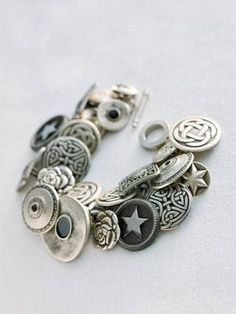 By Courtesy of Amy Barickman Start with a link bracelet (a nickel-plated version with a toggle clasp, 40 to 60 buttons with shanks (those small loops protruding from the backs), an equal quantity of jump rings, and a pair of needle-nose pliers. For each side of each link on the bracelet: Pry one jump ring open with the pliers, then thread the ring through both the button's shank and the link itself, and use the pliers to pinch it closed again. Repeat until the chain is filled with bottons