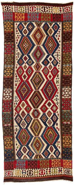 A large, white-ground Central Anatolian kilim composed of three panels: the field was woven as a single panel and the two borders woven separately and attached later. This approach avoids the misalignment of the design along the central axis that is so typical of two-panel Anatolian kilims. Judging by the clear and brilliant colours and balanced composition, this kilim is likely to date no later than the mid 19th century. Turkey