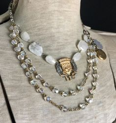 This triple-strand bib features a vintage Paris ship and wreath medal at its center, surrounded by hand wire-wrapped moonstone nuggets. I then hung a double layer of clear glass vintage rosary beads. Vintage silver toned watch chain slinks around the back, while a Victorian-style hand connector and my hand-forged hook and eye serve as an asymmetrical closure. Below this to the left side of the necklace hangs an old gold-filled locket into which I placed a sweet prayer card image, a genuine…