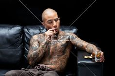 young criminal smoking and drinking - Young tattooed gangster smoking and drinking on couch over black background