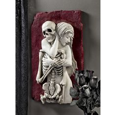 Life embraces death in this almost two-foot-high skeleton wall sculpture that beckons every eye in a room to its arresting subjects. From the hand-painted blood red background, alabaster flesh expresses rapture and encircles a bony skeleton in a bas relief sculpture.