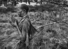 Gênesis | Etnia San - Um caçador segurando uma abetarda-de-barriga-preta, uma ave nativa do sul da África. Botsuana, África. 2008.