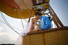 bride and groom kiss in hot air balloon