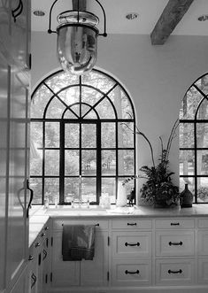 White kitchen with black hardware. Arched iron windows and wood beams.