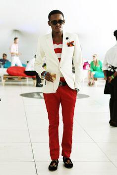 White blazer, red striped shirt, multi coloured pocket square, black lapel pin, black belt, red pants, skull moccasins