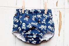 These trendy handmade retro baby bloomers are made from an awesome print of pirate skull and crossbones on a navy blue background. The external Retro Baby, Pirate Skull, Navy Blue Background, Baby Bloomers, Skull And Crossbones, Boho Shorts, Pirates, Trending Outfits, Awesome