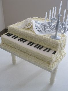 White Baby Grand Piano, Butter cream icing, gum paste flower and music, fondant keys.  Had white chocolate cover to prop on the piano but was afraid it would fall.  The cake was inspired from the candelabra that was a gift from a friend.  Cake was made for a choir get together.