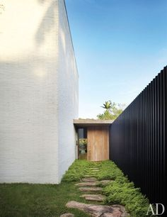 Architect Isay Weinfeld designed a home comprising six interconnected blocklike structures for an art-loving family in São Paulo, Brazil. A granite-flagstone path leads to the front entrance.