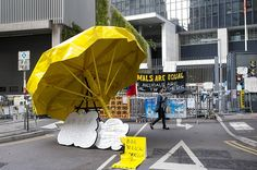Umbrella Revolution Hong Kong, A woman walks by a giant yellow umbrella -- a symbol of the pro-democracy protests in Hong Kong -- through the Occupy Camp in the Admiralty area of Hong Kong on November 17, 2014. A Hong Kong court notice ordering the eviction of democracy demonstrators from parts of the main protest site they have occupied for seven weeks has been published in leading newspapers on November 16, the first such public circular that empowers authorities to start clearing rally…