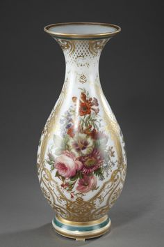 A baluster shape vase in white enamelled opaline, with polychromatic decoration composed of bunches of flowers on white background hightened with gilded arabesques and lattice. The collar an