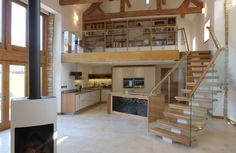 Oak framed kitchen cabinets with a classic matt white lacquered door sympathetically echo the oak roof trusses and plain white washed walls of this barn conversion. The angled island mirrors the lines of the staircase up to the mezzanine study which was designed to compliment the kitchen below.