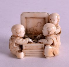 A 19TH CENTURY JAPANESE MEIJI PERIOD IVORY NETSUKE modelled as three children playing dice. 1.5ins wide.