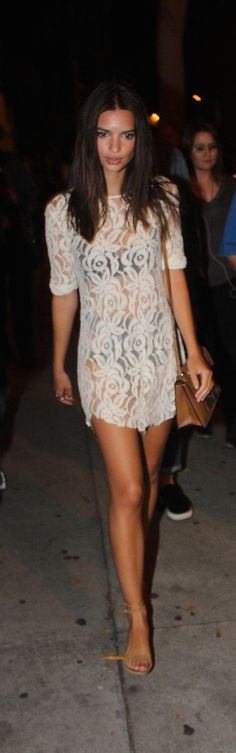 Emily Ratajkowski wears a lace cover-up over a black bikini with a brown crossbody  and tan sandals