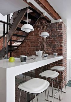 Nice open plan living area with chunky white breakfast bar and matching stools and repro (or very expensive original) Verner Panton Flowerpot lights against the urban living must, a brick wall and industrial stairs.
