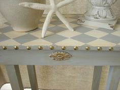 This listing is for a small vintage side table/accent table. This has been painted in a light grey with a harlequin design painted on top in cream & grey. I glazed it with aging glaze and added the brass tacks around the whole table. I added wood appliques and gold leafed them. This is the perfect piece for a coastal/cottage/rustic/shabby chic home. It adds a bit of rustic mixed with some elegance for a perfect mix. This table is very sturdy and measures 21.5 tall x 18...