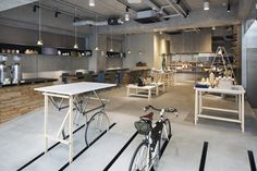 """RATIO&C is a cafe and shop by bicycle company Bridgestone Cycle; """"customers can park in clever slits in the floor and have their tires pumped as they sip coffee"""" (via Monocle magazine). This minimal space located in Tokyo, Japan, designed by TANK."""
