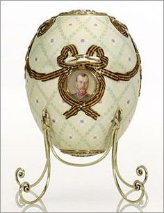 The Order of St. George Egg, one of the Nine Imperial Eggs. (1916). Made from enamel, gold, silver and rock crystal. The egg is encircled in gold and silver. Painted miniatures of previous honorees are revealed under their respective awards.