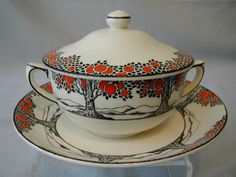 Vintage English art deco earthenware, manufacturered by A.G Richardson under the trademark Crown Ducal. The Orange Tree pattern was designed by Norman Keates in 1925. It was originally called Red Tree and consists of black tree silhouettes bearing bright orange fruit on a white ground, finished with a black trim.  Google Image Result for http://www.secretsartdeco.biz/uploads/Products/product_64/DSCN3689.JPG