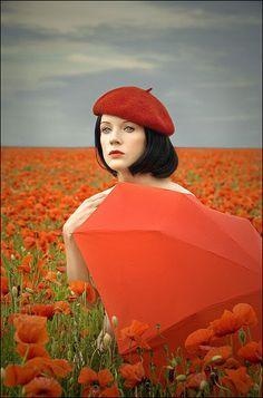 Orange parasol in a field of poppies