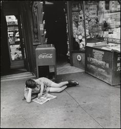 John Albok (1894-1982). Boy reading comics in front of newspaper store, west side of Madison Avenue between 96th and 97th Streets. 1933-1934. Museum of the City of New York. 82.68.11.