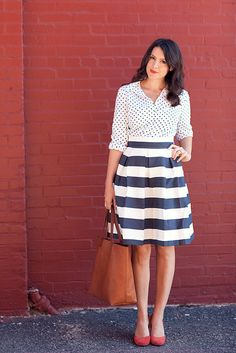 The pattern in the shirt is a small and delicate pattern. It blends in, in the distance and doesnt stand out compared to the bold skirt. The color scheme is an accented neutral. The pattern is black & white and the red shoes she have is the accent.