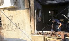An Israeli police officer inspects a house in the West Bank village of Duman that was badly damaged from a suspected attack by Jewish extremists.