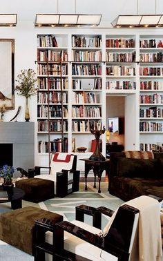 The floor-to-ceiling bookshelves in Diane von Furstenberg's Connecticut estate are highlighted by the Adnet armchairs, the abstract rug designed by Von Furstenberg herself, and a 1920s painting she found in Paris in the '70s.