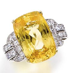 A yellow sapphire and diamond ring set with a cushion-shaped yellow sapphire weighing 19.01 carats, flanked by arched shoulders set with single-cut diamonds; mounted in platinum and eighteen karat gold