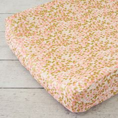 Complete the look of your nursery with the beautiful coral and gold sparkle changing pad cover.