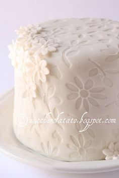 daisy cake- fondant with cutout shapes over same color frosting