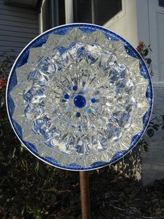 This is a garden art ornament designed to be hung from a stake in your yard. Also known as a plate flower. It has been hand crafted, from vintage bowls and plates that had a former purpose. A grouping of vintage glass, up-cycled or repurposed to make something new, a work of art.
