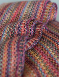 ...o think of this as Missoni-esque rather than clown barf. I cast on 600 stitches, and knitted through the back loops at the beginning and end of every row leaving a short length of yarn. I then pulled the yarn tightly to create a self-fringe. I did one row only per colour (which took 6-7 yards of yarn). I ended up doing 82 rows and the scarf is just over 6 inches wide. It grew in blocking and is about 9 ft long, and wraps twice round m...