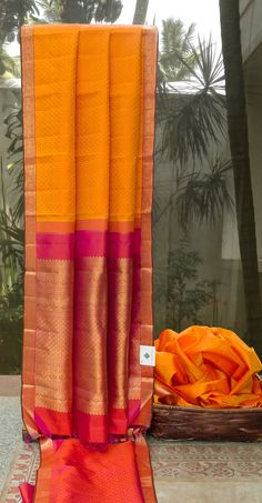 This light and breezy carrot orange colored kanchivaram silk has a jacquard pattern all over in candy orange thread work. The border and the pallu are in deep pink and have an intricately woven gol…