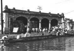 """La antigua Garita de la Viga en una toma de 1920, cuando ya estaba ocupada como bodega y vecindad. Al frente está el canal del mismo nombre, donde se aprecia una persona nadando, además de una embarcación que lleva el curioso nombre de """"El buque misterioso"""". De este espacio sólo queda el recuerdo; hoy es el cruce de La Viga y Chabacano."""