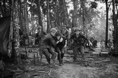 19 May 1969, A Shau Valley, South Vietnam --- Medics rush an injured paratrooper to an evacuation helicopter during fighting on 'Hamburger Hill' in the Vietnam War. --- Image by © Bettmann/CORBIS