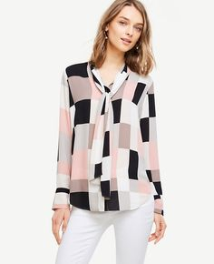 """Topped with a tie neck for endless styling possibilities, our colorblocked blouse carries you through the season - and beyond. Stand collar with neck ties. Long sleeves with button closure. Hidden button front. Shirttail hem. 26 1/4"""" long."""