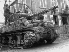 "Crew of a Sherman M4A3(76)W from the 14th Armored Division ""Liberators"" drive through a wired connection. For added protection against 'Panzerfaust', the tank was coated with sandbags. Rittershoffen, Alsace, north-eastern France. March 1945."