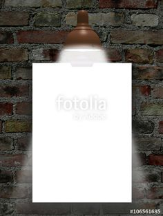 Close-up of one blank frame hanged by clip with lamp against dark weathered brick wall background