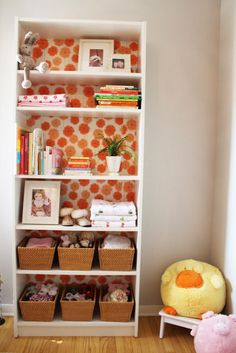 Cover the back of a bookshelf with bright patterned paper or fabric. (I am going to redo the old shelves in my classroom this way!)