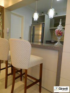 Bancada para cozinha em silestone cinza stellar e mdf Kaschmir, com poltronas e pendentes para dar um glamour ao ambiente.