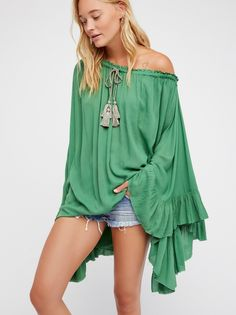 Here To Stay Tunic | Lightweight gauzy tunic in an oversized silhouette.    * Semi-sheer   * Elastic neckline with a tie tassel detail   * Off-the-shoulder style   * Dramatic statement sleeves with ruffle trim   * Unfinished edges
