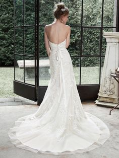 Maggie Sottero - WINSTYN, Dreamy lace and tulle combine to create this elegant fit and flare wedding dress; accented with timeless sweetheart neckline. A glittering Swarovski crystal motif on an optional grosgrain ribbon belt adds a touch of drama. Finished with covered buttons over zipper and inner elastic closure.