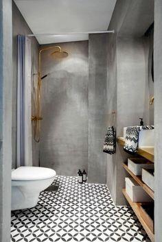 modele salle de bain, idée carrelage salle de bain, carrelage sol hexagonal en noir et blanc, murs en gris effet patiné, grande douche couleur or, rideaux de douche en lila et blanc, étagères en bois clair et niches de rangement