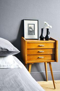 Un petit chevet vintage aux tons miel, sublimé par le gris des murs, qui donne chaleur et personnalité à cette chambre.