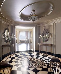 Tiled with Belgian marble, the foyer floor makes a dramatic statement; the George III mirrors and demilune tables are all from Kentshire Galleries | archdigest.com